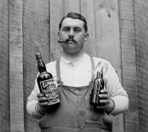 ca. 1900 --- A cigar smoking man poses with a bottle of whiskey and a bottle of beer, ca. 1900 --- Image by © DaZo Vintage Stock Photos/Images.com/Corbis