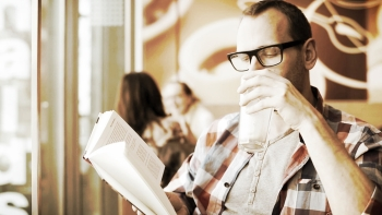 stock-footage-young-hipster-reading-book-drinking-coffee-in-cafe1