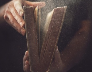 Holding an open book with dust coming out.