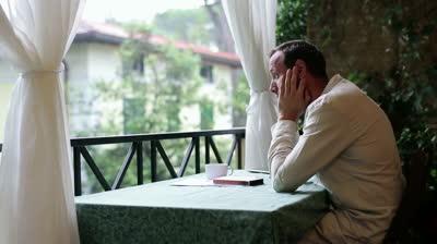 stock-footage-sad-man-sitting-alone-on-his-balcony